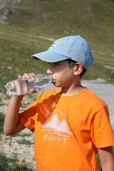 Young boy drinking water in a mountain landscape