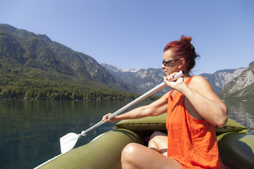 Woman paddle on calm mountain lake