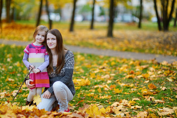 Young mother and her little daughter at fall