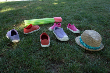 Kids beach shoes, hat and water gun on grass