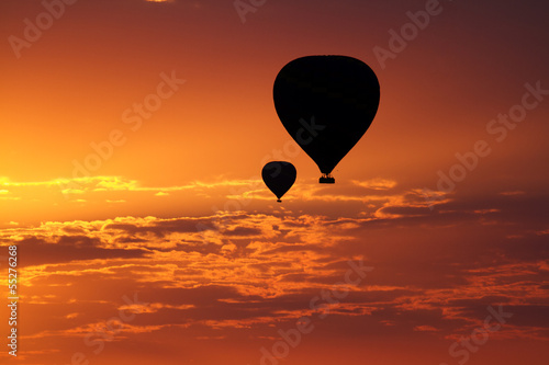 Balloons flying in early morning red sky