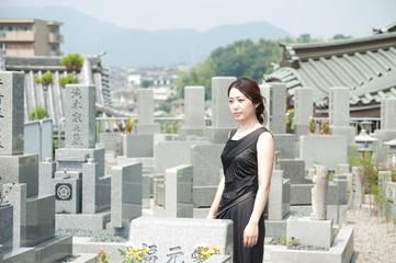 墓地で参拝する黒い服の女性