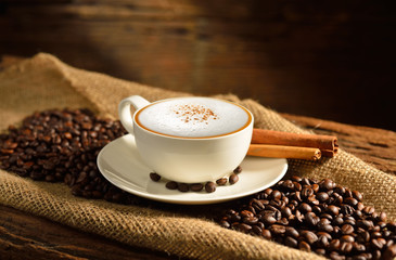 A cup of cappuccino and coffee beans on old wooden background © amenic181