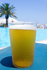 A glass of cold beer in front of the pool