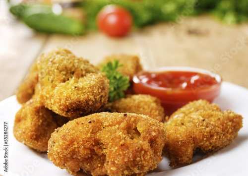 Fried chicken nuggets on the plate on the wooden table
