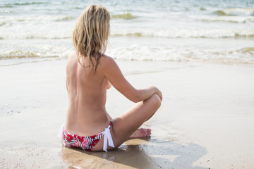 Young  topless girl relaxing next to the sea