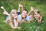 Happy children lying on the grass