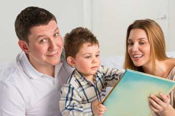 Parents Sitting With Child Reading Story Indoors