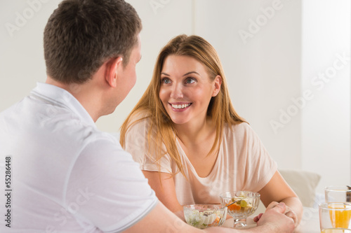Happy couple eating at home