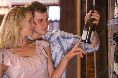 Young couple chooses the wine at supermarket