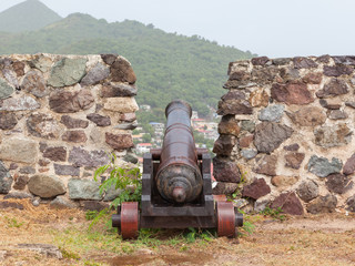 Very old rusted canon on top of an old wall