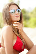 Young beautiful woman in red bikini and sunglasses at beach