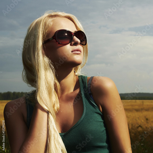 Beautiful blond girl on the field.beauty woman.sunglasses