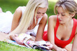 Two girls laying on the ground and reading magazines