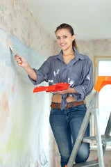 HAppy girl paints wall with brush