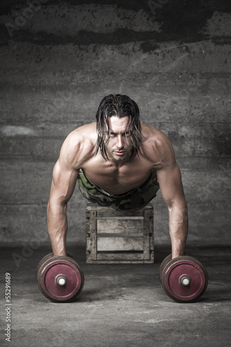 portrait of handsome longh hair athlete pushing up with weights