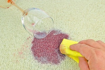 Cleaning up a spilled glass of red wine on a carpet