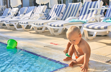 Kid playing in pool in hotel on background of of beach loungers