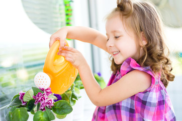 child watering flowers