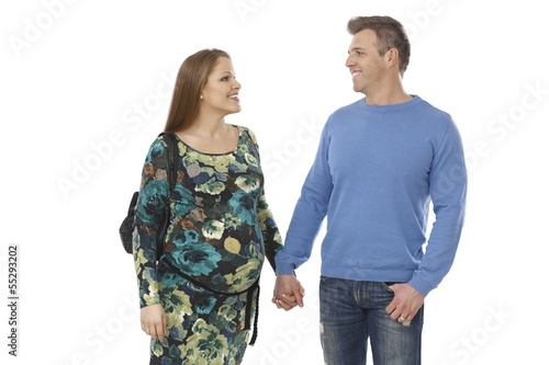 Expectant couple walking hand in hand