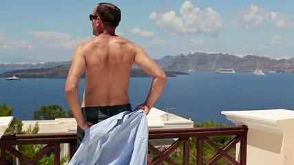 Man taking off shirt, relaxing on beautiful terrace