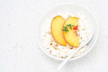 cottage cheese with honey, nuts, fresh peaches, thyme, top view