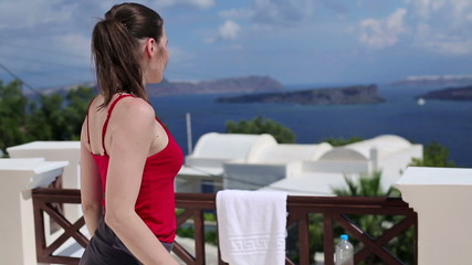 Tired woman drinking water after workout on terrace