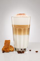 latte macchiato mit schokoladenpulver kaffee bohnen und keks