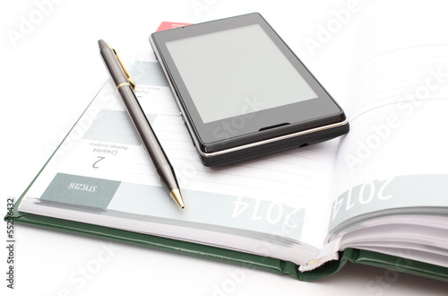 Modern mobile phone and pen lying on open calendar