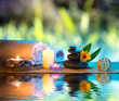 three candles and towels black stones and orange daisy on water