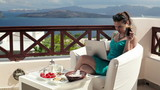 Woman with laptop during breakfast on beautiful terrace
