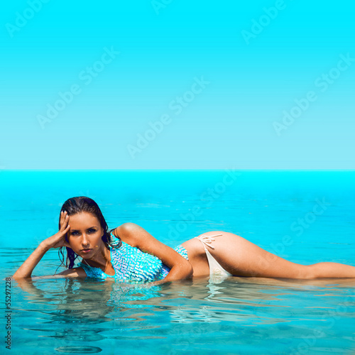 Hot brunette lying in blue water