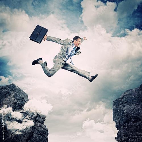 Biznesmen skacze nad przerwą