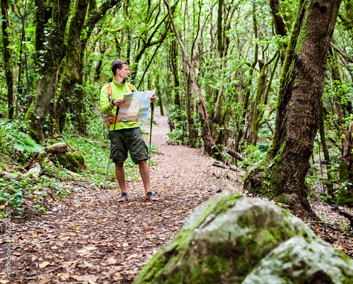 Hiker with map in forest