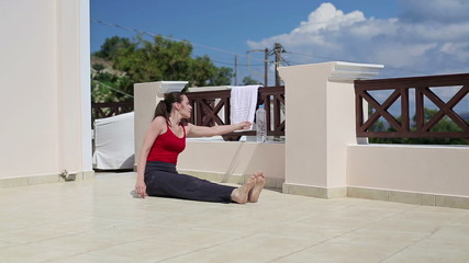 Young woman drinking water after stretching on terrace