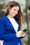 Smiling businesswoman texting on the phone