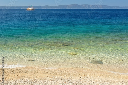 Beautiful beach with ship and island Hvar in background