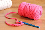 Pink zpagetti t-shirt yarn skein with a blue crochet hook