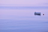 Lonely boat on flat surface of adriatic sea on calm morning poster