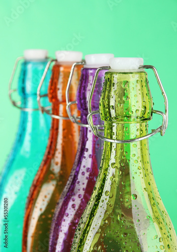Colorful bottles on green background