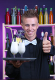 Portrait of handsome barman with Pina colada cocktail, at bar