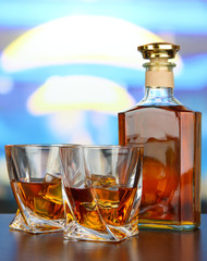 Glass of whiskey with bottle, on dark background