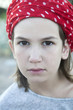 portrait of Unhappy little girl with  red scarf in spot