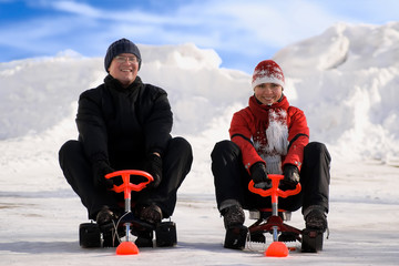 Happy young man and woman riding snowmobiles on winter snow hill