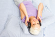 Blonde woman listening to music with headphones in the bed