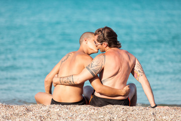 Gay couple is kissing in front of the beach