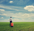 businessman with suitcase standing on field