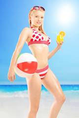 Young female in bikini holding a ball and cocktail, on a beach