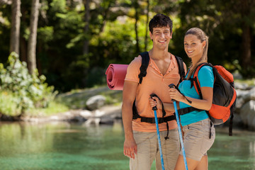 Portrait of couple with trekking outfit standing next to lake