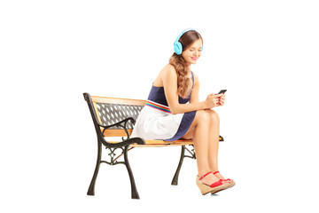 Young relaxing female sitting on a bench and listening music